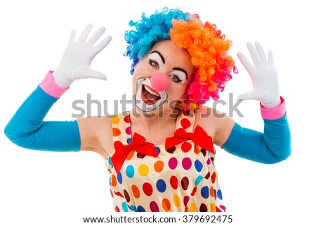 Portrait of a funny playful female clown in colorful wig teasing, looking at camera and showing palms, isolated on a white background - stock photo
