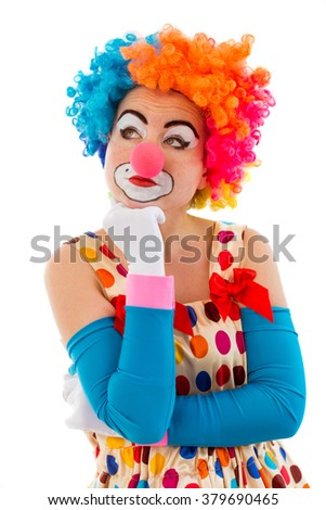 Portrait of a funny thoughtful female clown in colorful wig keeping hand on chin and looking away, isolated on a white background - stock photo