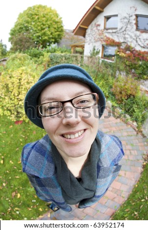 Portrait of a funny woman standing in the garden. Image taken with a fish-eye lens. - stock photo