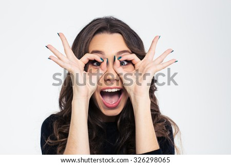 Portrait of a funny young girl looking at camera through fingers isolated on a white background - stock photo