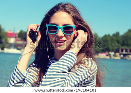 Portrait of a funny young girl on beach listening to music in earphones from smart phone mp3 player. Photo toned style Instagram filters - stock photo