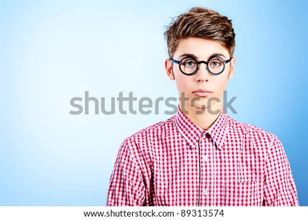 Portrait of a funny young man in spectacles. Over grey background.