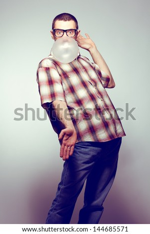 Portrait of a funny young man wearing trendy glasses, casual clothes posing over gray background and blowing his bubble gum. Hipster style. Studio shot - stock photo