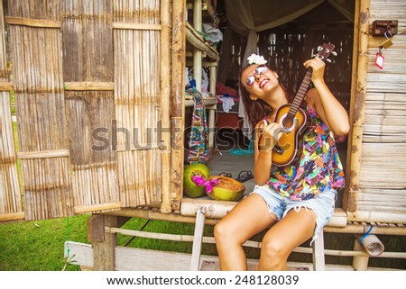 portrait of a funny young woman playing ukulele - stock photo