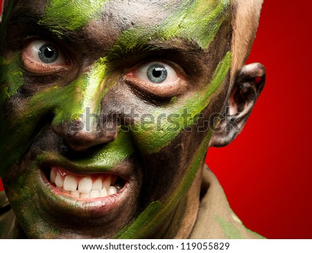 portrait of a furious soldier against a red background - stock photo