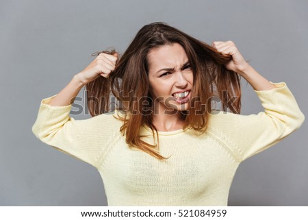 Portrait of a fustrated angry woman pulling her hair out isolated on the gray background