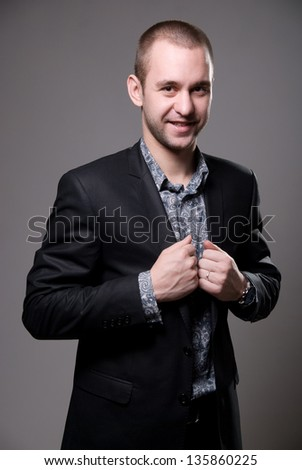 Portrait of a gay man looking at the camera on a gray background. - stock photo