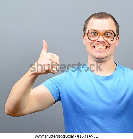 Portrait of a geek showing thumbs up against gray background - stock photo