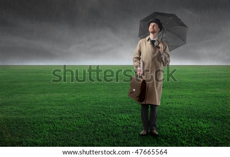 Portrait of a gentleman with an umbrella in his hand standing on a green meadow - stock photo