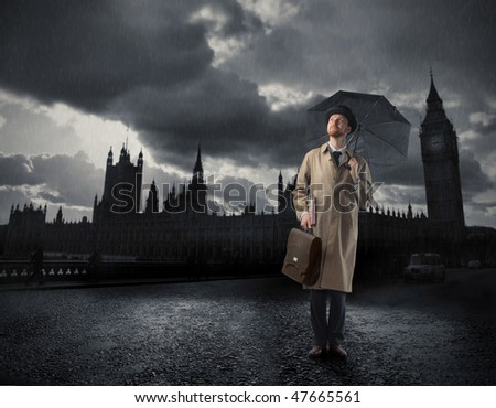 Portrait of a gentleman with an umbrella standing in front of the Big Ben - stock photo
