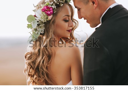 portrait of a girl and couples looking for a wedding dress, a pink dress flying with a wreath of flowers on her head on a background tsvetu chicago garden and the blue sky, and they hug and pose - stock photo