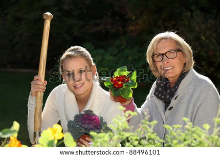 portrait of a girl and grandmother gardening - stock photo