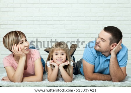 Portrait of a girl and her parents lying on a carpet in the living room. White brick wall background, space for text.
