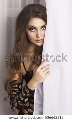 portrait of a girl behind the curtain