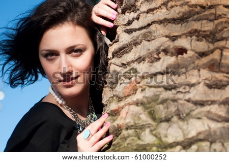 Portrait of a girl behind the palm tree trunk - stock photo