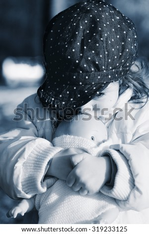 Portrait of a girl, being sad and lonely. Little girl crying and holding her puppet. - stock photo