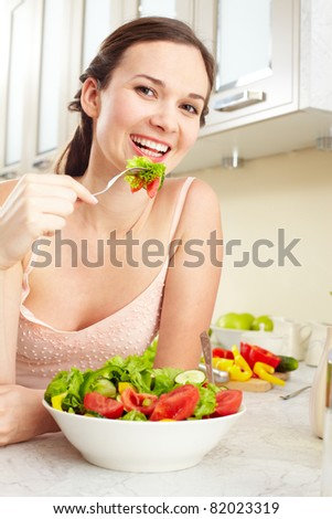 Portrait of a girl eating salad and looking at camera