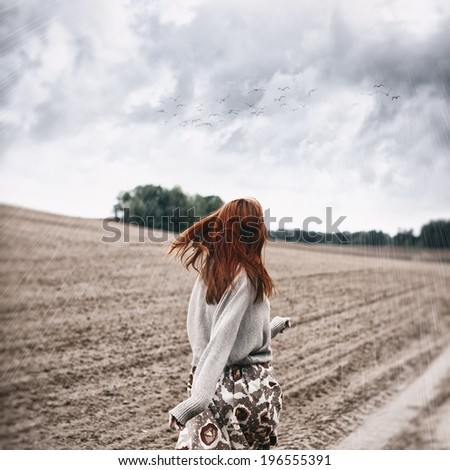 Portrait of a girl from behind in bad weather on the field - stock photo