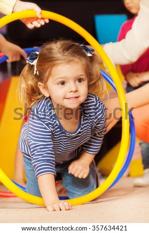 Portrait of a girl go though hoop in active game - stock photo