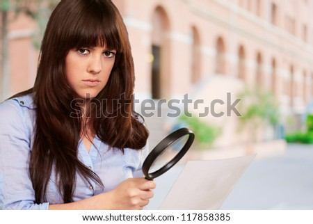 Portrait Of A Girl Holding A Magnifying Glass And Paper, Outdoor - stock photo