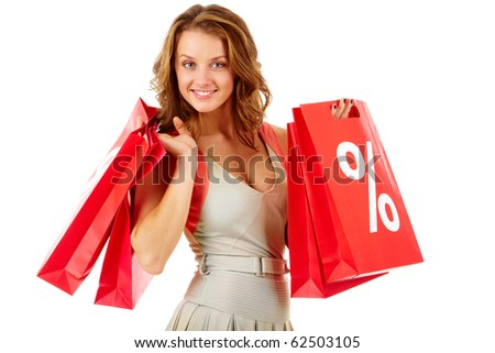 Portrait of a girl holding handbags with discount symbol, looking at camera and smiling - stock photo