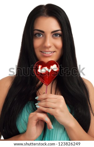 Portrait of a girl holding heart shape candy - stock photo