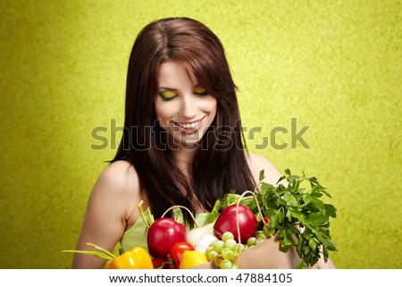 Portrait of a girl holding in hands full of different fruits and vegetables
