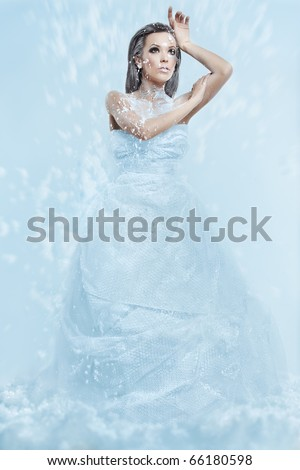 portrait of a girl in a blizzard of snow that looks like a snow queen - stock photo