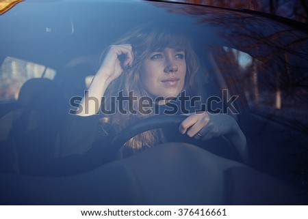 portrait of a girl in a car driver at the wheel - stock photo