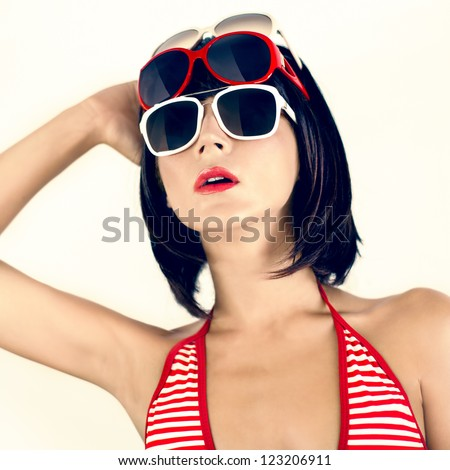Portrait of a girl in a fashionable swimsuit and sunglasses - stock photo