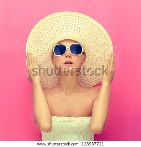 portrait of a girl in a hat on a pink background - stock photo