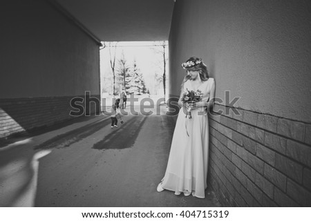 Portrait of a girl in a white dress against the wall.