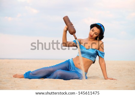 Portrait of a girl in belly dance costume with the old clay bottle - stock photo