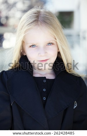 Portrait of a girl in black dress. Charming child with air baloons posing on white background indoors. Studio shot - stock photo