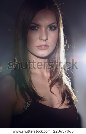 Portrait of a girl in bright light studio dark background - stock photo