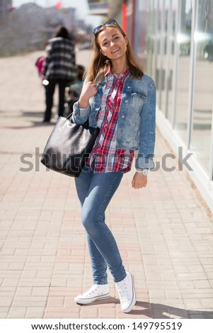 portrait of a girl in full growth in jeans on the street - stock photo