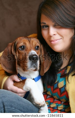Portrait of a girl in her twenties posing with a young purebred beagle pup.
