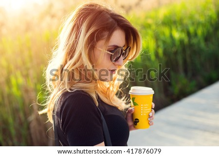 Portrait of a girl in sunglasses with a paper cup of coffee . Shooting at sunset