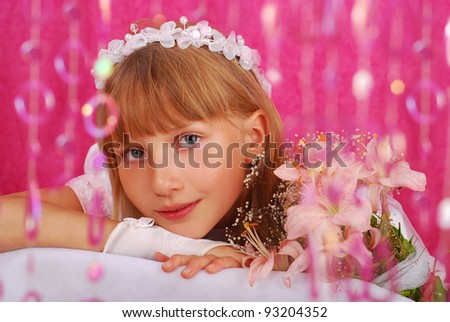 portrait of a girl in white dress and wreath ,going to the first holy communion and posing in studio against pink background - stock photo