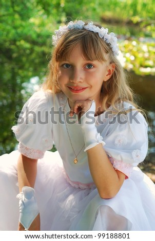 portrait of a girl in white dress and wreath ,going to the first holy communion and posing in park - stock photo