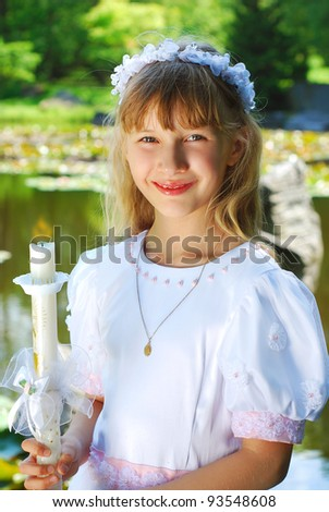 portrait of a girl in white dress and wreath ,going to the first holy communion and posing in the park with candle - stock photo