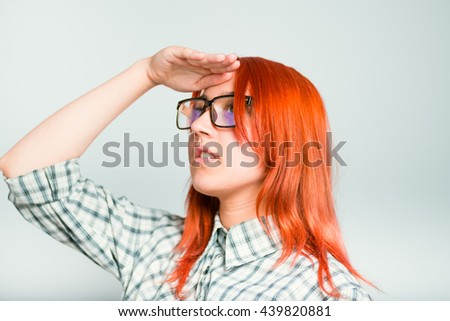Portrait of a girl looking into the distance, future, the redhead with glasses, isolated on a gray background - stock photo