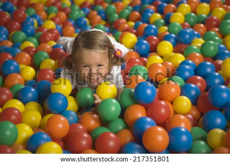 Portrait of a girl lying in a ball pool and smiling - stock photo