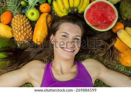 Portrait of a girl lying on the grass with fruits and vegetables - stock photo