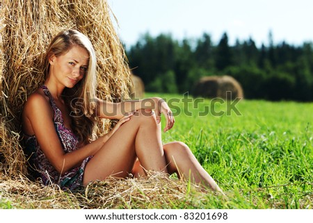 portrait of a girl next to a stack of hay - stock photo