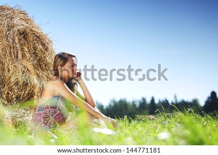 portrait of a girl next to a stack of hay under the blue sky