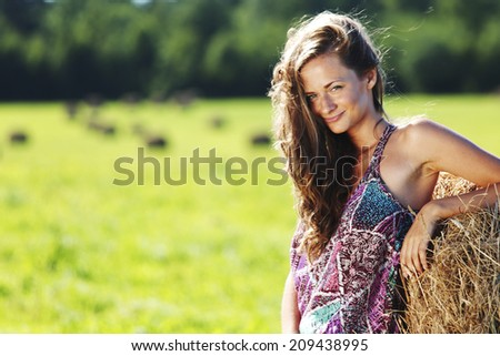 portrait of a girl next to a stack of hay under the blue sky - stock photo