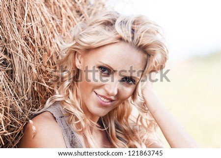portrait of a girl next to haystack close - stock photo