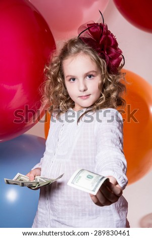 Portrait of a Girl offers money dollars looking forward to the camera. School girl on a background of large rubber balls. Offer to take the money. - stock photo