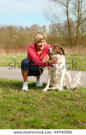 Portrait of a girl playing with a dog outdoors. - stock photo
